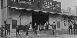 An old photo of Clovis Livery and Feed shop with men and horses in front